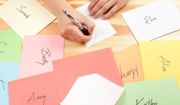 Close up of hand with pen addressing cards